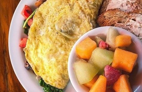 Desayuno de tortilla de verduras con huevos camperos, tostadas y fruta.