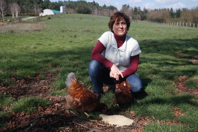 Nuria Varela-Portas junto a dos de sus gallinas camperas alimentándose de pienso, en Pazo de Vilane.