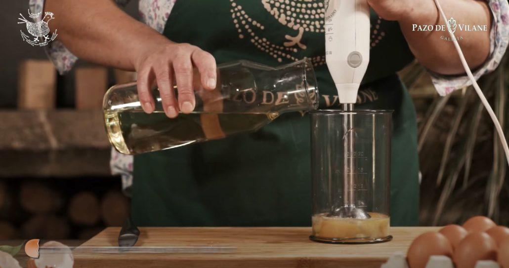 Añadiendo aceite de oliva a los huevos camperos para montar la mayonesa casera