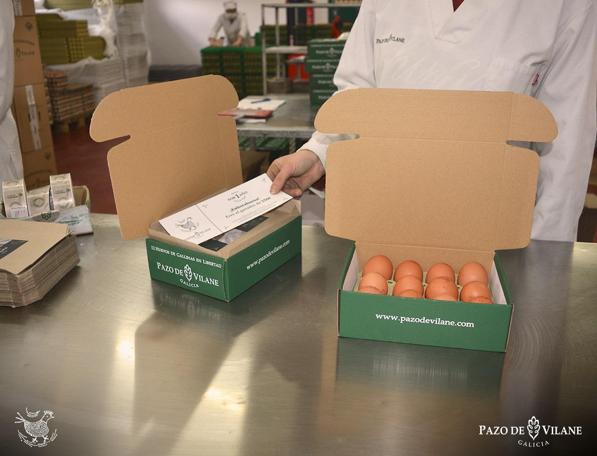Una empleada de Pazo de Vilane introduce uno de los cheques regalo Huevos por 1 año en una de las cajas de huevos camperos de Pazo de Vilane.